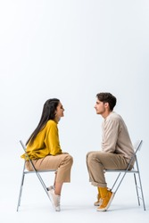 side view of handsome man sitting on chair near cheerful woman on white