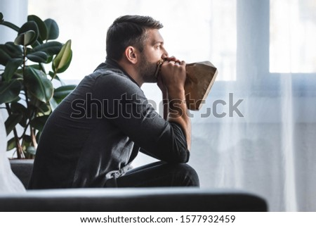side view of handsome man with panic attack breathing in paper bag in apartment  Stock photo ©