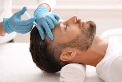 Side view of handsome middle aged man getting hair treatment at beauty salon. Man having mesotherapy session at aesthetic clinic, therapist hands in gloves making injection in scalp, closeup