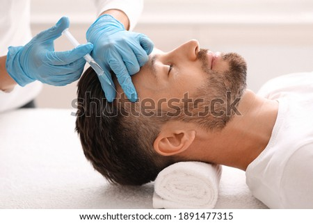 Side view of handsome middle aged man getting hair treatment at beauty salon. Man having mesotherapy session at aesthetic clinic, therapist hands in gloves making injection in scalp, closeup Foto stock ©