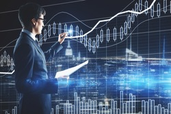 Side view of handsome young european businessman with document in hand drawing forex chart on blue city background. Finance concept