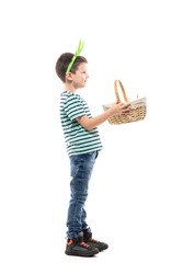 Side view of happy boy giving away basket full of Easter eggs hunt. Full length isolated on white background.