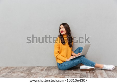 Side view of happy brunette woman in sweater sitting on the floor with laptop computer and looking back over gray background