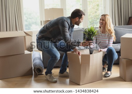 Side view of happy Caucasian couple unpacking cardboard box in new home #1434838424