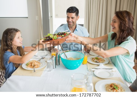 Side view of happy family of three sitting at dining table in the home