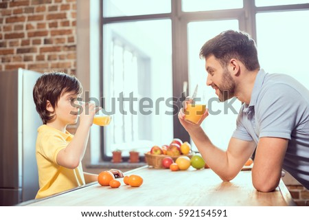 Side view of happy father and son drinking fresh juice together  #592154591
