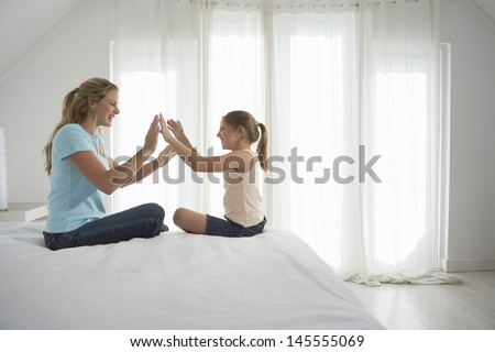Side view of happy mother and daughter playing patty-cake on bed #145555069