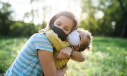 Side view of happy mother hugging small daughter in nature, wearing face masks.