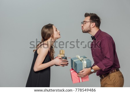 side view of happy young couple holding gift boxes and able to kiss isolated on grey #778549486