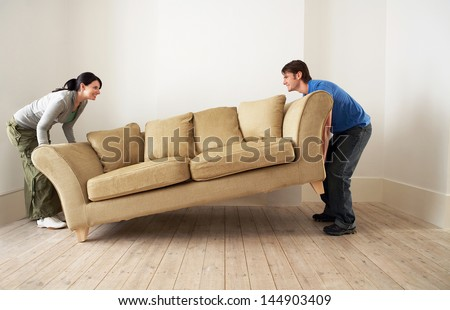 Side view of happy young couple placing sofa in living room of new home