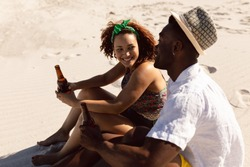 Side view of happy young Mixed-race couple with beer bottle talking with each other on beach in the sunshine