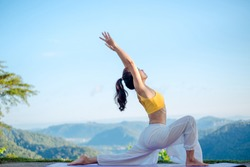 Side view of healthy women practicing yoga. standing in Warrior I pose.asana Anjaneyasana - low crescent lunge pose. in surya namaskar. beautiful landscape view sky on morning.