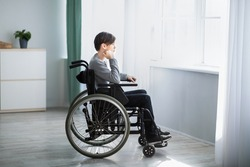 Side view of impaired teenage boy in wheelchair feeling desperate and lonely, looking out window at home