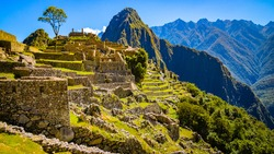 Side view of Inca city of Machu Picchu, near Cusco, Peru. The terraces are nicely visible. Blue skies.  Unesco World Heritage site, one of the new wonders of the world.