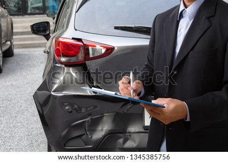 Side view of insurance officer writing on clipboard while insurance agent examining black car after accident.