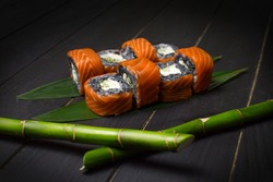 Side view of Japanese black rice sushi roll with salmon on top served on green bamboo leaves with bamboo sticks out of focus on foreground. Cucumber and cream cheese wrapped in rice. inside out roll