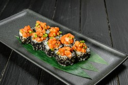 Side view of Japanese sushi volcano roll with black flying fish roe (tobiko). Marinated salmon and spring onions on top. Served on bamboo leaves on black plate. Dark wooden background