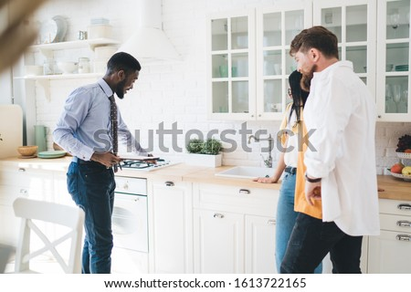 Side view of joyful business African American realtor presenting new kitchen to young buyers in big light flat and touching cookstove