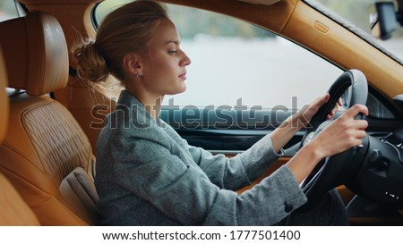 Side view of joyful business woman dancing in car in slow motion. Confident businesswoman listening music at car. Successful girl moving behind steering wheel at car. Photo stock ©