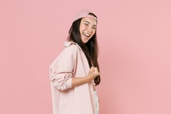 Side view of joyful young asian woman 20s in casual clothes cap posing isolated on pastel pink background studio portrait. People emotions lifestyle concept. Mock up copy space. Doing winner gesture