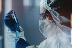 Side view of laboratory technician wearing safety goggles and mask and pipetting out chemical mixture to test tube. Clinical researcher developing effective anti-coronavirus vaccine or treatment