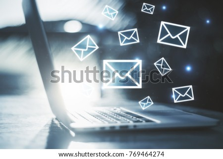 Side view of laptop with e-mail interface on blurry background. Email marketing concept
