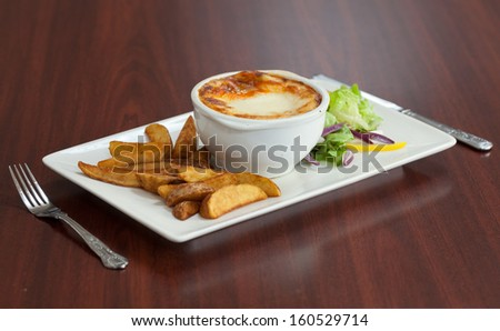 Side view of lasagna with salad and potatoes on wooden table