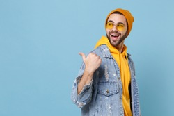 Side view of laughing young hipster guy in fashion jeans denim clothes posing isolated on pastel blue background studio portrait. People lifestyle concept. Mock up copy space. Pointing thumb aside