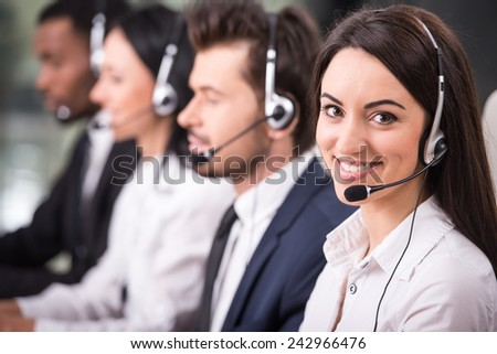 Side view of line of call centre employees are smiling and working on computers.