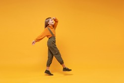 Side view of little kid girl 12-13 years old in turtleneck, jumpsuit isolated on yellow background. Childhood lifestyle concept. Mock up copy space. Holding hand at forehead looking far away distance