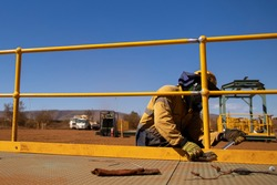 Side view of maintenance worker wearing working uniform safety fall protection helmet hand glove using vise grip and adjustable wrenches spanner when tightening bolt nut onto handrail kickboard