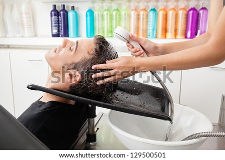Side view of male customer having hair washed at salon