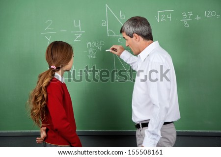 Side view of male professor teaching mathematics to female student on board in classroom #155508161