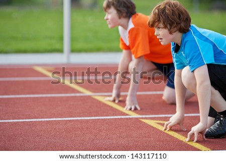 Side view of male runners on starting position at racetrack