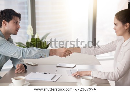 Side view of man and woman partners shaking hands over the table, maintaining eye contact, confident entrepreneurs ready for effective negotiations, entering into a partnership, gender equality