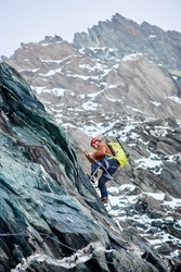 Side view of man climber with backpack using fixed rope to climb high rocky mountain, ascending alpine ridge and trying to reach mountaintop. Concept of mountaineering and alpine rock climbing.