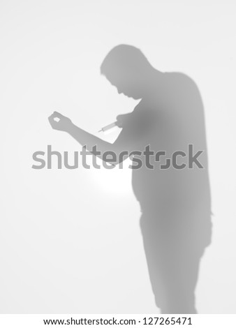 side view of man holding a syringe towards his arm behind a diffuse surface