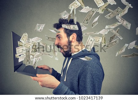 Side view of man holding laptop and winning plenty of money in social media.