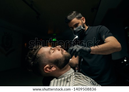Side view of man sitting in chair and covered with striped gown while his handsome barber in black gloves concentrated on shaving beard using razor. Concept of professional service at barbershop