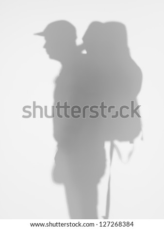 side view of man with backpacker and a cap on his head behind a diffuse surface