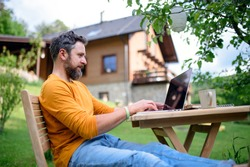 Side view of man with laptop working outdoors in garden, home office concept.