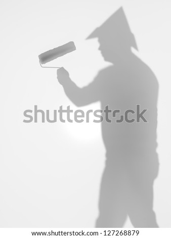 side view of man with paint roller in his hand and a hat  in shape of tringle on his head, behind a diffuse surface