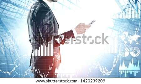 Side view of man with phone standing over skyscraper background with double exposure of business infographics. Market analysis concept. Toned image. Elements of this image furnished by NASA #1420239209