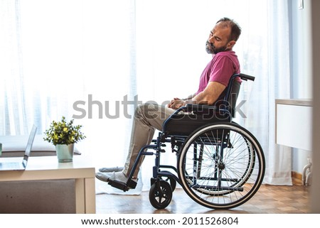 Side view of mature man sitting in wheelchair and looking away. Side view of thoughtful disabled active Caucasian man looking through window on wheelchair in a comfortable home Foto stock ©