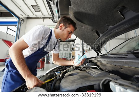 side view of mechanic checking motor oil