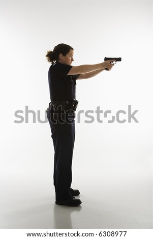 Side view of mid adult Caucasian policewoman standing and aiming handgun.