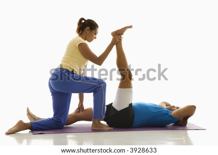Side view of mid adult multiethnic woman assisting mid adult multi-ethnic man with stretching on exercise mat.