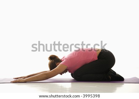 Side view of mid adult multiethnic woman wearing exercise clothing in childs yoga pose.