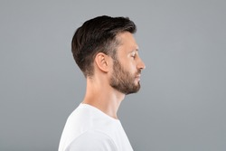 Side view of middle-aged bearded man in white t-shirt over grey studio background, copy space. Profile portrait of handsome man with closed eyes posing on gray, standing straight and looking aside