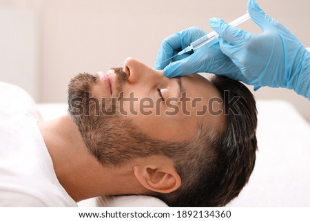 Side view of middle-aged man getting beauty injection in nose at aesthetic clinic. Plastic surgeon injecting anti-aging filler in handsome bearded man nose, having plastic correction, closeup